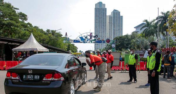 Petugas kepolisian memberhentikan kendaraan di pintu masuk Taman Impian Jaya Ancol, Jakarta Utara, Sabtu (15/5). Pengelola Ancol menutup seluruh area rekreasi dan wisatanya selama sehari guna penyemprotan disinfektan dan evaluasi penguatan protokol kesehatan. Foto: Ricardo - JPNN.com